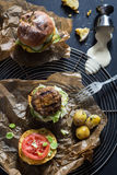 Homemade Juicy Pork Burger, a Veggie One with a Flag Topper and Buttered Baby Potatoes with Dill Royalty Free Stock Photos