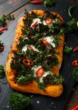 Homemade Kale and red chilli flatbread pizza with mozzarella.  royalty free stock photo