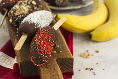 Homemade kids dessert: frozen bananas. Homemade kids dessert. Frozen banana lollipops covered with chocolate, nuts, sprinkles over wooden board. Selective focus Royalty Free Stock Images
