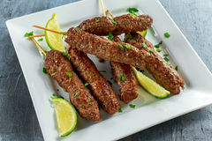 Homemade Kofta kebabs on skewers with lime and parsley on white plate Stock Photography