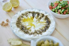 Homemade labneh labaneh. Middle eastern soft white goat`s milk cheesewith olive oil ,hyssop , salt, Arabic fresh salad , olives served at traditional dinner stock image