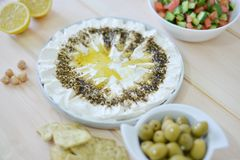 Homemade labneh labaneh. Middle eastern soft white goat`s milk cheesewith olive oil ,hyssop , salt, Arabic fresh salad , olives served at traditional dinner royalty free stock image