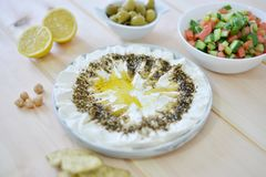 Homemade labneh labaneh. Middle eastern soft white goat`s milk cheesewith olive oil ,hyssop , salt, Arabic fresh salad , olives served at traditional dinner stock photos