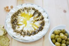 Homemade labneh labaneh. Middle eastern soft white goat`s milk cheesewith olive oil ,hyssop , salt, Arabic fresh salad , olives served at traditional dinner royalty free stock photography