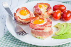 Baked eggs in bacon cups Stock Photos