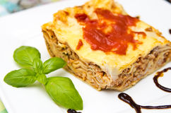 Homemade lasagna on white plate and colorful tablecloth Royalty Free Stock Photos