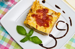 Homemade lasagna on white plate and colorful tablecloth Stock Images