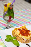 Homemade lasagna on white plate and colorful tablecloth Royalty Free Stock Photography
