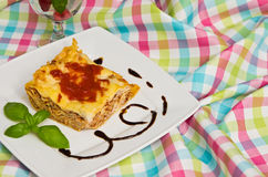 Homemade lasagna on white plate and colorful tablecloth Stock Photography