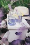 Homemade lavender lemonade with fresh lemons on a white wooden tray Royalty Free Stock Photo