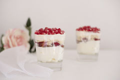 Homemade layered dessert with mascarpone, chocolate, cream, fresh strawberries, cookies, pomegranate. Cheese in a glass. Stock Image