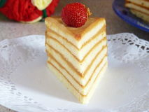 Homemade Layered Sponge Cake. Piece of Layered Sponge Cake Decorated with Strawberry and Walnut Royalty Free Stock Photography