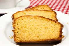 Homemade lemon drizzle cake. A slice of freshly made lemon drizzle cake with a cup of coffee stock photos