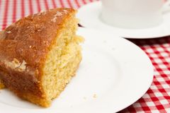 Homemade lemon drizzle cake. A slice of freshly made lemon drizzle cake with a cup of coffee royalty free stock images