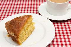 Homemade lemon drizzle cake. A slice of freshly made lemon drizzle cake with a cup of coffee royalty free stock image