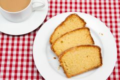 Homemade lemon drizzle cake. A slice of freshly made lemon drizzle cake with a cup of coffee stock images