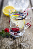 Homemade lemonade with fresh berries on a wooden table.Cocktail Stock Image