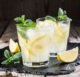 Homemade lemonade with fresh lemon and mint. On a wooden background Stock Image