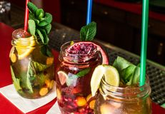 Homemade lemonade ice tea colorful icetea drink with fresh sweet fruits mint leaves in glass on the rocks with straw Royalty Free Stock Photos