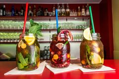 Homemade lemonade ice tea colorful icetea drink with fresh sweet fruits mint leaves in glass on the rocks with straw Royalty Free Stock Images