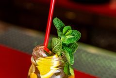 Homemade lemonade ice tea colorful icetea drink with fresh sweet fruits mint leaves in glass on the rocks with straw Royalty Free Stock Photo