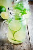 Homemade lemonade with lime, mint in a mason jar on a wooden table Stock Photos