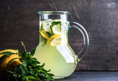 Homemade lemonade with mint, lemon slices and ice over dark background, copy space Stock Images