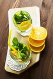 Homemade lemonade with orange and mint. Cold lemonade with orange and mint in a glass. Selective focus. Top view Stock Photos