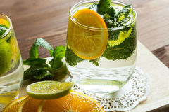 Homemade lemonade with orange and mint. Fresh homemade lemonade with orange and mint on the background of an old wooden board. Selective focus Royalty Free Stock Image