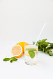 Homemade lemonade with water, lemon and mint leaves in a glass on a white background. Royalty Free Stock Photo