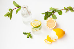 Homemade lemonade with water, lemon and mint leaves in a glass on a white background. Royalty Free Stock Photos