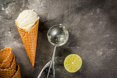Homemade lime sorbet. Homemade lemon ice cream. Horn with sorbet, sprinkled with zest, spoon and half lime. On a gray concrete old table. Top view copy space stock photos