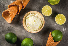 Homemade lime sorbet. Refreshing lime sorbet in a bowl with a spoon for ice cream. With cones for ice cream one full of ice cream, limes, grater for peel. On an Royalty Free Stock Image