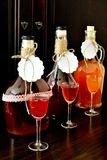 Homemade liqueur in bottles and glasses. Closeup of homemade colorful liqueurs in bottles and glasses on a dark brown background. Roses, raspberries and apricots stock photo