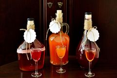 Homemade liqueur in bottles and glasses Royalty Free Stock Image