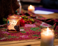 Homemade lit candles. On a floral fabric Stock Image