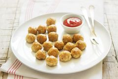 Homemade little chicken meatballs with tomato sauce on a wooden table. royalty free stock images