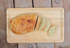 Homemade loaf of bread on wooden board. Homemade loaf of bread and slices on wooden board Stock Photography