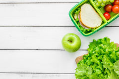 Homemade lunch with apple, grape and sandwich in green lunchbox top view mockup Stock Photos