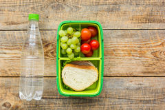 Homemade lunch with bottle, grape and sandwich in green lunchbox top view mockup Stock Image