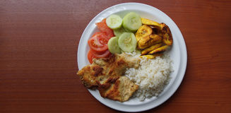 Homemade lunch consisting of chicken puffed with white rice, fried banana, tomato slices and cucumber served on a white plate. Homemade lunch consisting of Stock Image