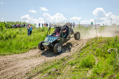 Homemade machine built with tuning rally buggy rides with the driver and co-driver at high speed past the spectators along the du Royalty Free Stock Images