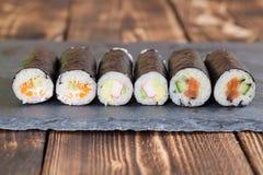 Homemade maki sushi rolls. On a slate board stock photography