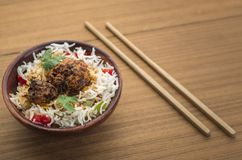 Manchurian with cooked rice in a bowl. Homemade manchurian and cooked rice with sauces in a wooden background Royalty Free Stock Image
