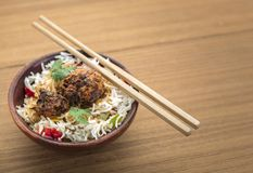 Manchurian with cooked rice in a bowl. Homemade manchurian and cooked rice with sauces in a wooden background Royalty Free Stock Images