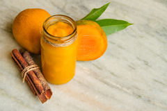 Homemade Mango Jam with fresh fruits and slices mango, cinnamon sticks on a white marble. Royalty Free Stock Images