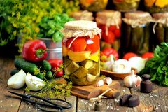 Homemade marinated assorted with tomato, cucumber and squash, dill, carrot, garlic and onion in a jar on an old wooden background. royalty free stock photography