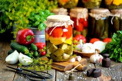 Homemade marinated assorted with tomato, cucumber and squash, dill, carrot, garlic and onion in a jar on an old wooden background. stock photography