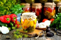 Homemade marinated patissons with dill, carrots, garlic and onions in a jar on an old wooden background. Rustic style. royalty free stock images