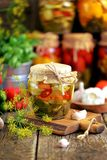Homemade marinated zucchini with chili, dill, carrots, garlic and onions in a jar on an old wooden background. Rustic style. royalty free stock photo